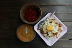 Gebratenes Basilikumblatt mit Huhn und Spiegeleier auf Reis in hölzernem b stockfotografie
