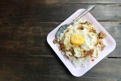 Gebratenes Basilikumblatt mit Huhn und Spiegeleier auf Reis in hölzernem b lizenzfreies stockbild