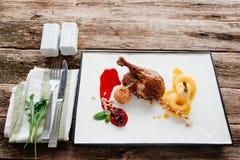 Gebratenes Entenbein mit Birne und Tischbesteck stockbilder