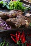 Gebratenes Fleisch mit Zwiebeln, Knoblauch, Gewürzen, frischen Kräutern, rotem Pfeffer und Salz Lizenzfreies Stockbild