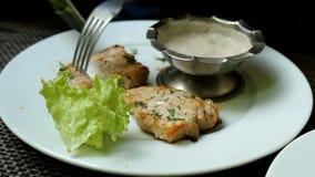 Gebratenes Fleisch wird mit einem Messer geschnitten, um auf einer Gabel zu stechen, eingetaucht in Soße und gegessen stock footage