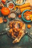 Gebratenes ganzes angefülltes Huhn oder Truthahn für Danksagungs-Tagesabendessen mit Soße, Kürbisen, Mais und Herbst ernten Gemüs Stockbild