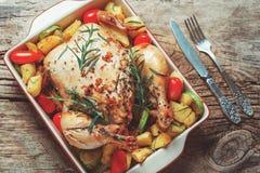 Gebratenes ganzes Huhn angefüllt mit Gemüse, Tomatenkartoffelpfeffer und Rosmarin auf Weinleseholztisch Lizenzfreie Stockfotografie