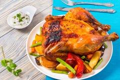 Gebratenes ganzes Huhn mit Kartoffeln, Babykarotten, Auberginen und grünen Bohnen auf der weißen runden Serviette des Tellers auf Lizenzfreies Stockfoto