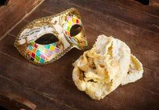 Gebratenes Gebäck des italienischen Karnevals mit venetianischer Maske stockbilder