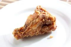 Gebratenes Hühnerbein auf weißem Teller Lizenzfreies Stockfoto