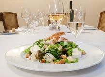 Gebratenes Hühnerbein mit Salat Stockbild