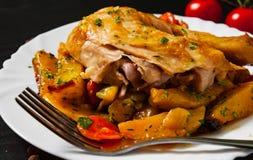 Gebratenes Hühnerbeine mit Karotten, Zwiebeln und Kartoffeln dienten auf einer weißen Platte Lizenzfreies Stockbild