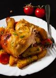 Gebratenes Hühnerbeine mit Karotten, Zwiebeln und Kartoffeln dienten auf einer weißen Platte Stockfotografie