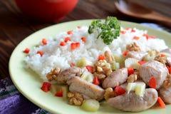 Gebratenes Hühnerfleisch mit Stielsellerie, gebratene Walnüsse und Reis Stockfoto
