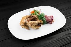 Gebratenes Huhn auf einer weißen Platte Schwarzer hölzerner Hintergrund Stockfoto