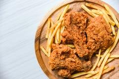 Gebratenes Huhn knusperig auf hölzernem Behälter mit Pommes-Frites auf Draufsicht des Speisetischhintergrundes stockfoto