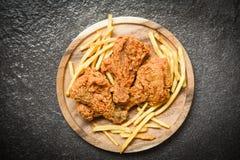 Gebratenes Huhn knusperig auf h?lzernem Beh?lter mit Pommes-Frites auf dunklem Hintergrund lizenzfreie stockfotos