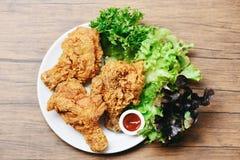 Gebratenes Huhn knusperig auf wei?er Platte mit dem Ketschup- und Salatkopfsalat Gem?se auf h?lzernem stockbilder