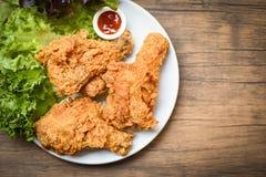 Gebratenes Huhn knusperig auf weißer Platte mit Ketschup- und Salatkopfsalatgemüse auf hölzernem Hintergrund lizenzfreie stockfotos