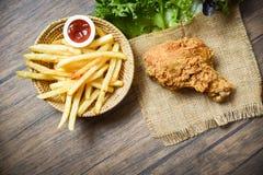 Gebratenes Huhn knusperig und Salatkopfsalatsack mit Pommes-Friteskorbketschup auf hölzernem Speisetischhintergrund lizenzfreie stockfotografie
