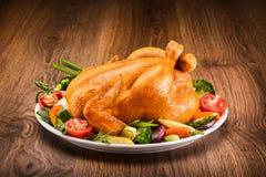 Gebratenes Huhn mit Gemüse auf einem Holztisch stockbilder