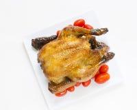 Gebratenes Huhn mit geschnittenen Orangen- und Kirschtomaten Lizenzfreie Stockfotos