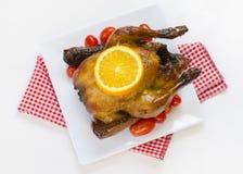 Gebratenes Huhn mit geschnittenen Orangen- und Kirschtomaten Stockfotografie