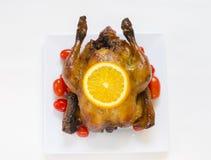 Gebratenes Huhn mit geschnittenen Orangen- und Kirschtomaten Stockfotos