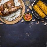 Gebratenes Huhn mit Reis auf einem Schneidebrett, einer scharfen Soße, Gewürzen, einem Knoblauch und einem Mais in der Wanne auf  Stockfoto