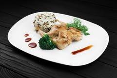 Gebratenes Huhn mit Risotto auf weißer Platte Stockfoto