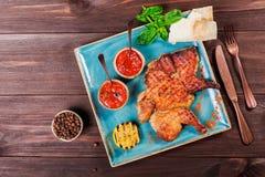Gebratenes Huhn oder Truthahn mit Gewürzen, Zitrone, Tomatensauce, Basilikum und Pittabrot auf Platte auf dunklem hölzernem Hinte Lizenzfreie Stockfotos