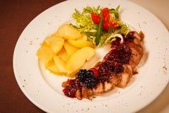 Gebratenes Rindfleisch mit Kartoffel, Tomatensalat und Moosbeerbehandlung Lizenzfreies Stockbild