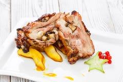 Gebratenes Schweinefleisch angefüllt mit Pilzen, Pfirsich, Carambola, Moosbeeren und süßer Soße auf Platte auf hölzernem Hintergr stockbild