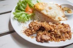 Gebratenes Schweinefleisch mit knusperigem Knoblauch auf Reis + Spiegelei Stockbild