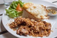 Gebratenes Schweinefleisch mit knusperigem Knoblauch auf Reis + Spiegelei Lizenzfreies Stockfoto