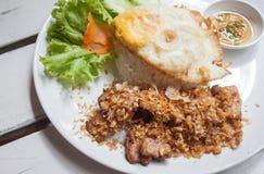 Gebratenes Schweinefleisch mit knusperigem Knoblauch auf Reis + Spiegelei Stockbilder
