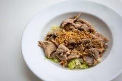 Gebratenes Schweinefleisch mit knusprigem Knoblauch, Pfeffer und Gemüse auf weißem Cer Lizenzfreies Stockbild