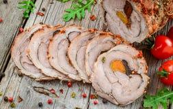Gebratenes Schweinefleisch-Rolle angefüllt mit getrockneten Aprikosen, Käse und Walnüssen stockbild
