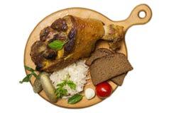 Gebratenes Schweinefleischbein diente mit dem Sauerkraut, das auf Weiß lokalisiert wurde Stockbilder