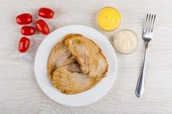 Gebratenes Schweinefleischschnitzel in der Platte, Tomaten, Schüsseln mit Majonäse, Stockfotografie