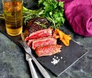 Gebratenes Steak, Grüns, briet Kartoffeln und Bier, Messer und Gabel auf einem dunklen Hintergrund Stockfotografie
