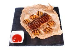 Gebratenes Steak mit Kartoffeln auf Papier und Tomatensauce in einer Schale auf einem schwarzen Brett auf einem lokalisierten wei stockbild