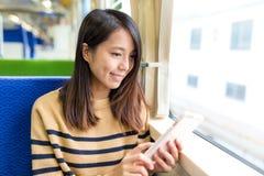 Gebrauch der jungen Frau von Handy auf Zug Lizenzfreies Stockbild