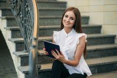 Gebrauch des jungen Mädchens eine Tablette und ein Telefon zu arbeiten Das Mädchen im Café lächelt lizenzfreies stockbild