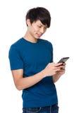 Gebrauch des jungen Mannes des Smartphone für die Prüfung von E-Mail Stockfotos
