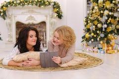 Gebrauch des modernen Geschenkgeräts durch zwei Schwestern, die auf Boden im brigh liegen lizenzfreies stockbild