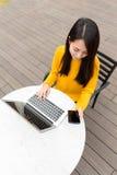 Gebrauchs-Laptop-Computer der jungen Frau und intelligentes Telefon Lizenzfreies Stockfoto