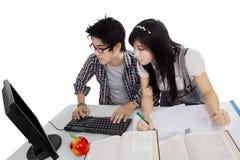 Gebrauchscomputer mit zwei Studenten auf Schreibtisch Lizenzfreie Stockbilder