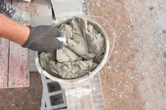 Gebrauchsfertiger Zement und alte Schaufeln an einer Baustelle schöpfen Stockfotografie