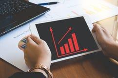 Gebrauchstablette der berufstätigen Frau für Arbeit mit Geschäftszusammenfassungs- oder Unternehmensplanbericht mit Diagrammen un Lizenzfreies Stockbild