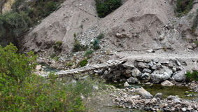 Gebrechliche Wegbrücke über felsigem Nebenfluss Stockfoto