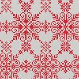 Gebreid naadloos patroon van witte sneeuwvlokken op een rode achtergrond Royalty-vrije Stock Foto