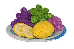Gebreide citroenen en druiven op een plaat Royalty-vrije Stock Foto's