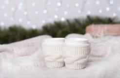 Gebreide koppen met thee over Kerstmislicht Royalty-vrije Stock Afbeeldingen